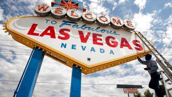 """In this July 28, 2005, file photo, an electric company worker changing ballasts and lamps on the """"Welcome to Las Vegas,"""" sign in Las Vegas."""