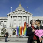 Gay rights advocates John Lewis, left, and his spouse Stuart Gaffney, with the group Marriage Equality USA, kiss across the street from City Hall in San Francisco, Friday following a ruling by the U.S. Supreme Court that same-sex couples have the right to marry nationwide.