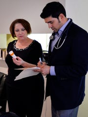 Dr. Romin Shah, right, goes over medications with Diana