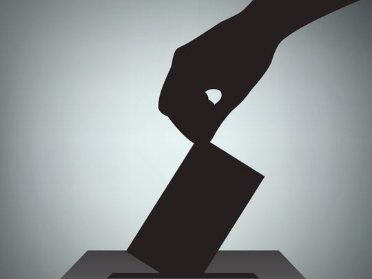 Hand with voting ballot and box.