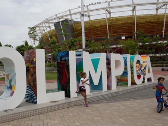 In this Feb.4, 2017 photo, children play near the Olympic Park sign in Rio de Janeiro, Brazil. Rio organizers still owe creditors about $40 million. Four of the new arenas in the main Olympic Park have failed to find a private-sector management, and ownership has passed to the federal government. Another new arena will be run by the cash-strapped city.