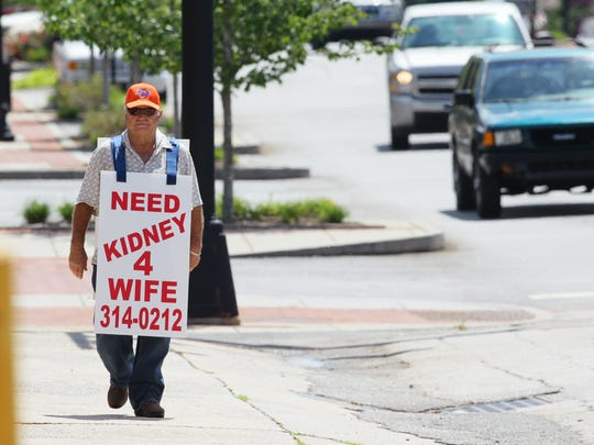 In this 2012 picture, Larry Swilling walks north on Main Street in Anderson to attract a kidney donor for his wife, Jimmie Sue Evans Swilling.