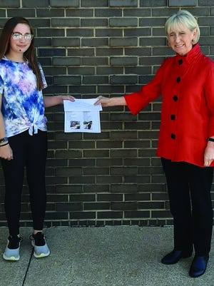 Kate Killian-Johnson presents a check to Macomb Junior High Principal, Dana Isackson.