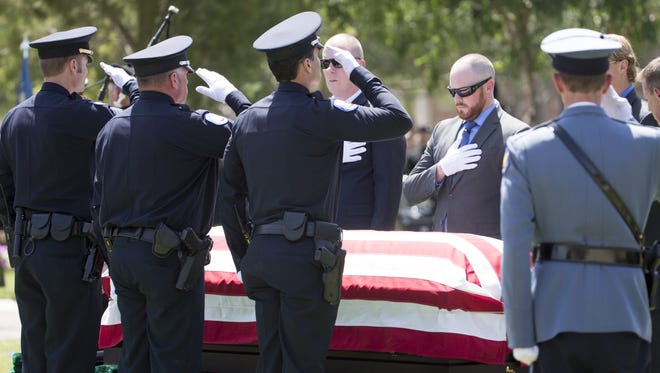 Pallbearers honor Phoenix Officer David Glasser  as he is laid to rest at Phoenix Memorial Park and Cemetery.