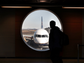 A traveler admires a jet outside a window at the Keflavik