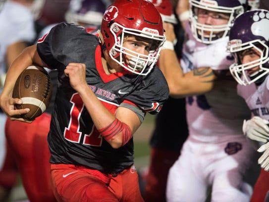 Halls's quarterback Caden Tollett tries to get past