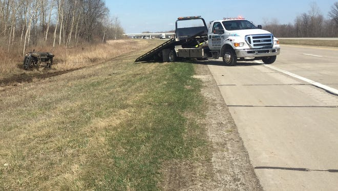 A tow truck gets ready to remove a flipped SUV that went off Interstate 69 after its driver over-reacted to a roadside rumble strip.