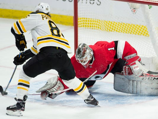 Boston Bruins right wing David Pastrnak (88) tries to stick-handle the puck around Ottawa Senators goaltender Mike Condon (1) during the first period of an NHL hockey game Thursday, Jan. 25, 2018, in Ottawa, Ontario. (Adrian Wyld/The Canadian Press via AP)