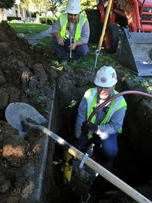 Lancaster Municipal Gas employee Craig Dupler pressure tests a service line Tuesday on Fair Avenue in Lancaster as Jared Roley waits above ground with a tool to tap the main line.