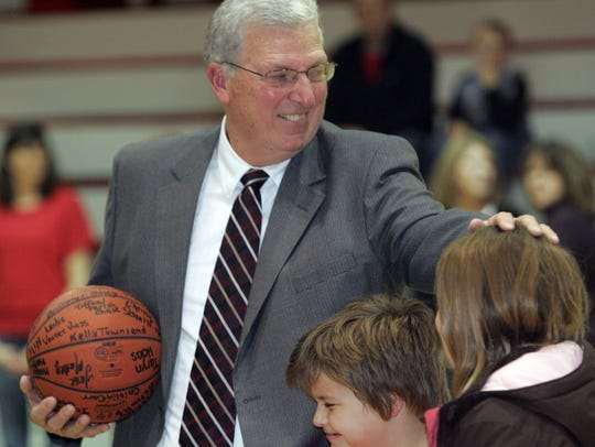 Elgin coach Bill McElroy clutches a ball signed by