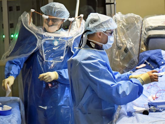 Dr. Arshad Safi, an interventional cardiologist, left, performs coronary stent surgery on a patient Tuesday, February 14, 2017 at Chambersburg Hospital.