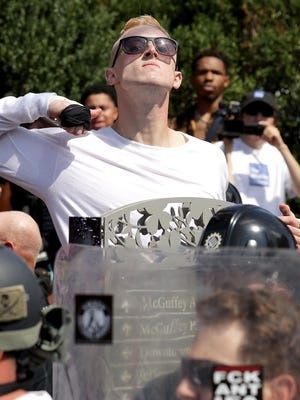 """An unidentified man makes a slashing motion across his throat toward counter-protesters Aug. 12, 2017, as he marches with other white nationalists, neo-Nazis and members of the """"alt-right"""" during the """"Unite the Right"""" rally in Charlottesville, Va."""