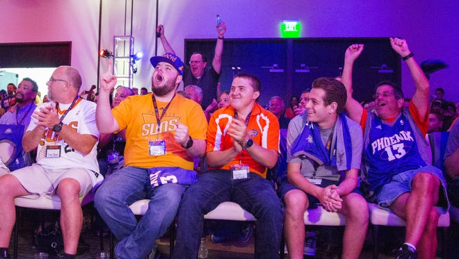 Kenny Fillipone (left center in orange) and his friend Anton Hansen (to his right in orange) celebrate as the Suns draft Devin Booker with the 13th pick during the Suns' draft party at the Palomar Hotel in Phoenix, AZ on June 25, 2015.