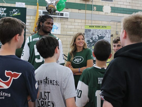 New York Jets player Lorenzo Mauldin talks with students