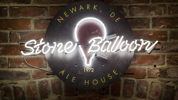 A neon Stone Balloon sign hangs in the interior of