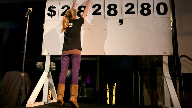 Lucy Cooper, 12, of Stevens Point unveils the amount of money raised during the 2015 United Way campaign during the United Way of Portage County's Victory Celebration at the Grand Hall at SentryWorld in Stevens Point, Wednesday, Dec. 2, 2015. Team Cooper was the 2015 Drive Chair Family. The goal for the 2015 campaign was  $2,800,000.