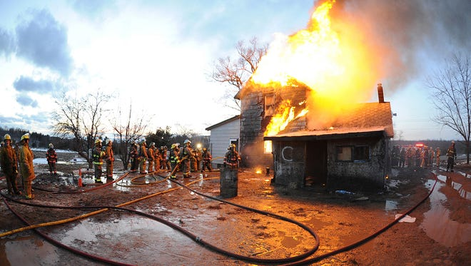 Firefighters lined up April 15, 2013, to enter a burning house in Arpin, where the Arpin Volunteer Fire Department held live fire training. Similar training will take place in Wisconsin Rapids beginning Monday.