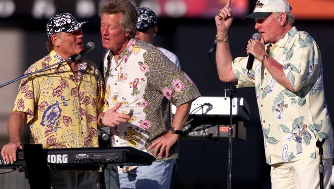 The Beach Boys' Bruce Johnson, left, and Mike Love, right, sing with Dean Torrence, center, from the duo, Jan and Dean, classic hits dealing with surfing and hot rod cars for fans at Grizzlies Stadium in Fresno, Calif., Sunday, May 5, 2002. (AP Photo/The Fresno Bee, Tomas Ovalle)