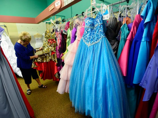 Barb Moran-Engler, co-owner of A Personal D'Signs bridal store, looks through dresses in the store.