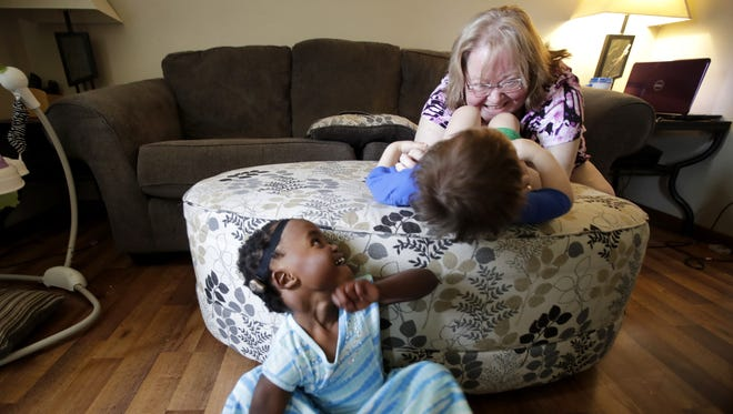 Tess Piasecki, 3, looks up as her mother, Mindi, tickles her brother Adam, 1, on June at their home in Neenah. Tess and Adam were both adopted and the family is hoping to adopt a third child.