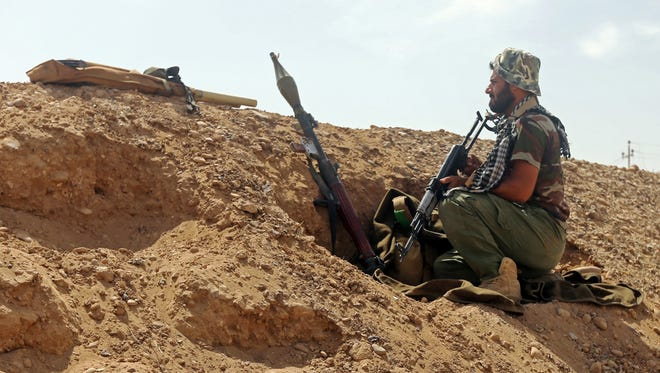An Iraqi fighter from the popular mobilization unit keeps position in al-Nibaie area, northwest of Baghdad on May 27, 2015, during an operation aimed at cutting off Islamic State militants in Anbar province before a major offensive to retake the city of Ramadi.