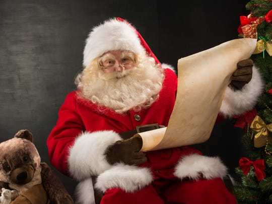 Portrait of happy Santa Claus sitting at home reading a Christmas letter or wish list.