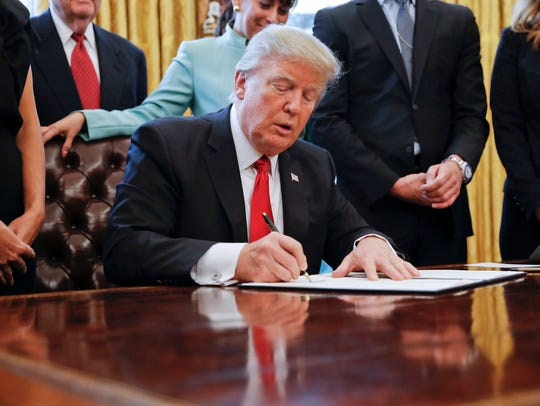 President Trump signs an executive order in the Oval