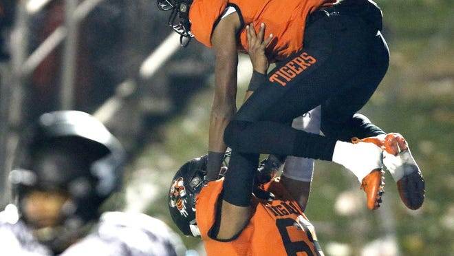 Massillon's Andrew Wilson -Lamp is lifted up in celebration by lineman Terrence Rankl after scoring a first half touchdown against Perry.