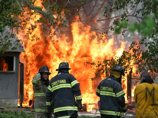 Firefighters from Christiana Fire Company stand by as a vacant home and its outbuildings are allowed to burn after a day of training was completed.