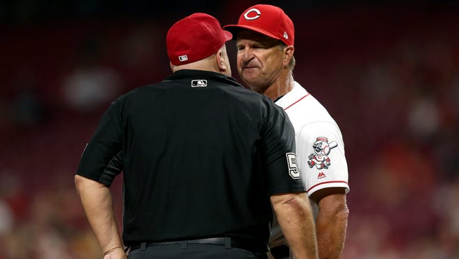 Cincinnati Reds interim manager Jim Riggleman (35), right, and umpire Eric Cooper (56), left, argue as Riggleman is ejected in the 12th inning during an interleague baseball game between the Chicago White Sox and the Cincinnati Reds, Tuesday, July 3, 2018, at Great American Ball Park in Cincinnati.