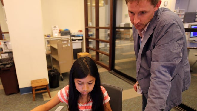 White Plains Librarian Erik Carlson helps Mariana Naulaguari, 11, create a cube on the computer during a 3-D printing camp at the White Plains Public library on July 11, 2016.