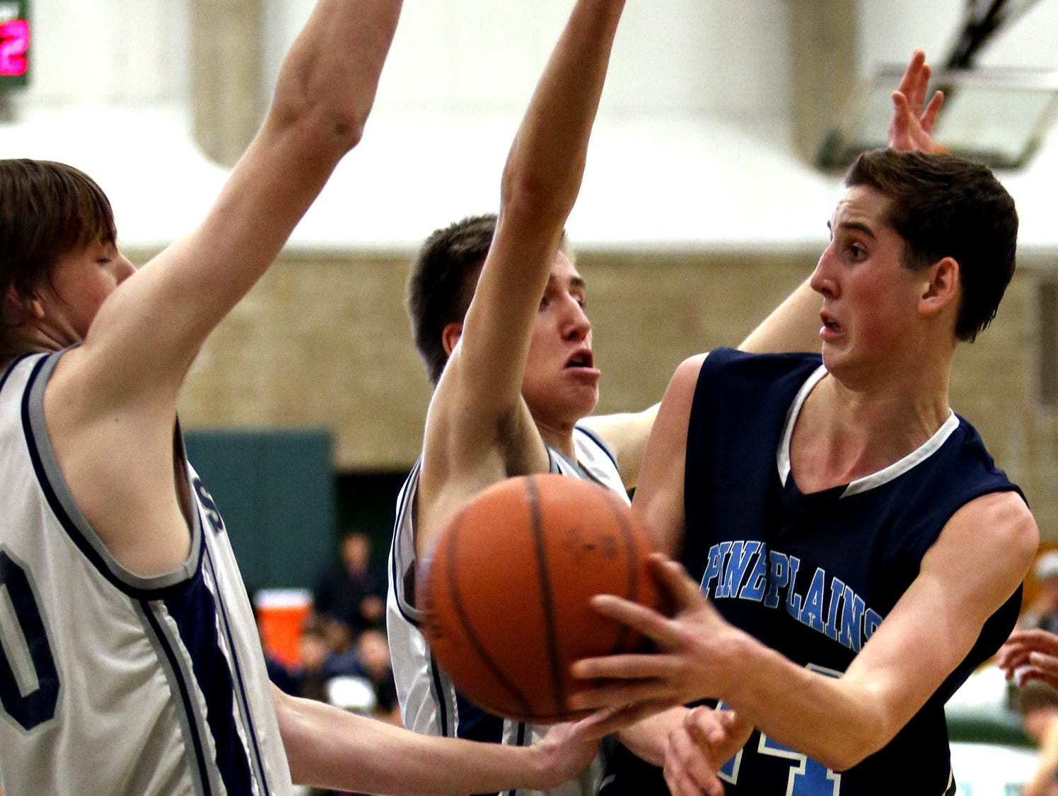 Pine Plains' Tyler Lydon dishes between Stony Brook School's Andrew Daniel, left, and Max Pitsch in a Class C state regional final at Old Westbury on March 9, 2013.