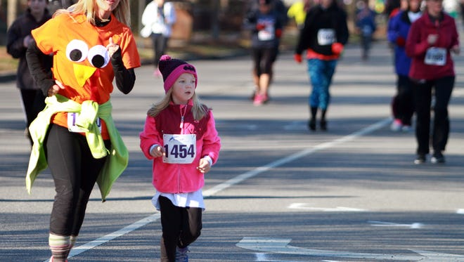 Runners make a turn to head towards the finish line at the Indian Lake Loop run on Thanksgiving Day in Hendersonville.