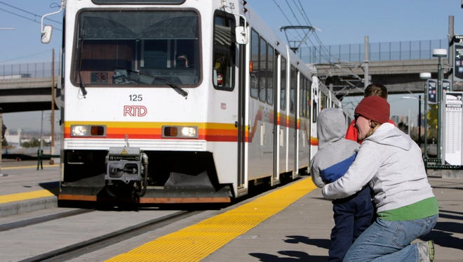 Jill Cooper, right, holds her 3-year-old son, Wyatt, as a Regional Transportation District light rail train arrives at the Broadway station in south Denver in 2006.