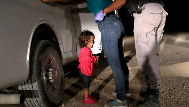 A two-year-old Honduran asylum seeker cries as her mother is searched and detained near the U.S.-Mexico border on June 12, 2018 in McAllen, Texas. The asylum seekers had rafted across the Rio Grande from Mexico and were detained by U.S. Border Patrol agents before being sent to a processing center for possible separation.