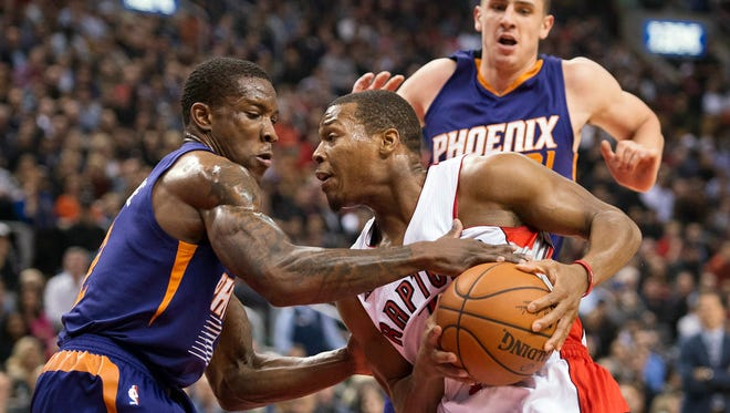 Toronto's Kyle Lowry drives to the basket between Suns Eric Bledsoe (left) and Alex Len during the first half on Monday, Nov. 24, 2014.