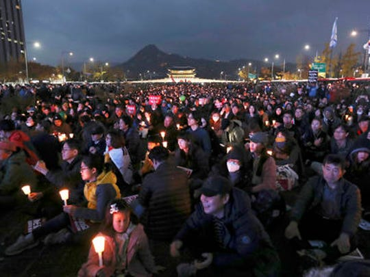 FILE- In this Saturday, Nov. 12, 2016, file photo, South Korean protesters hold up candles during a rally calling for South Korean President Park Geun-hye to step down in Seoul, South Korea. Tens, and possibly hundreds, of thousands of South Koreans marched in Seoul on Saturday demanding the ouster of President Park Geun-hye in one of the biggest protests in the country since its democratization about 30 years ago.