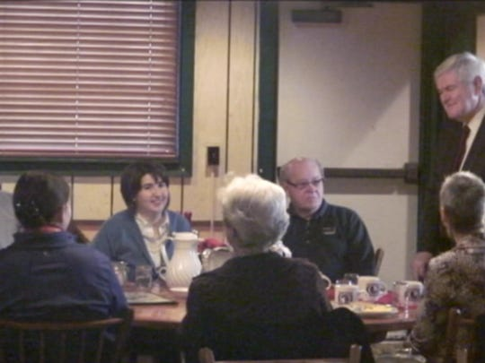 Newt Gingrich chats with a table of Iowans at Urbandale's Iowa Machine Shed restaurant.