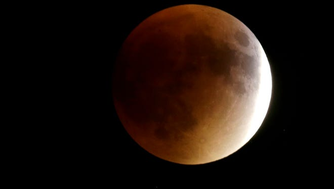 Earth's shadow begins to obscure the view of a so-called supermoon during a total lunar eclipse Sunday, Sept. 27, 2015, in Lecompton, Kan. It's the first time the events have made a twin appearance since 1982, and they won't again until 2033. (AP Photo/Orlin Wagner)