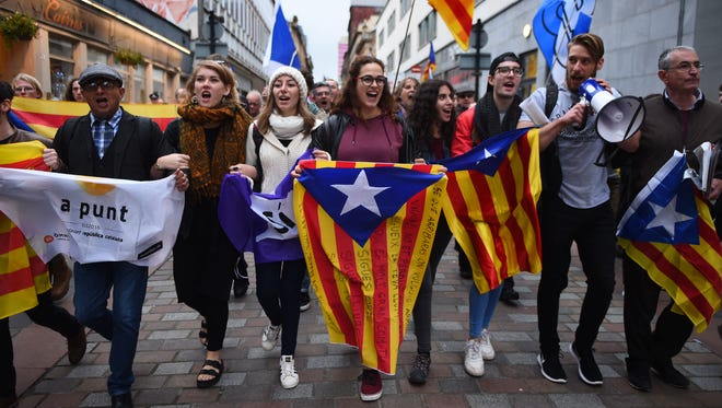 """Demonstrators display the Catalan Flag, the Senyera during a march to show solidarity with Catalonia, in Glasgow on Oct. 9, 2017. The Scottish National Party on Oct. 10, 2017 urged the Spanish government to """"respect the overwhelming 'si' vote"""" in the Catalan independence referendum."""