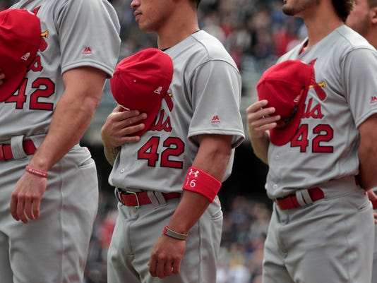 St. Louis Cardinals players all wear the number 42 as they stand on the base line for the national anthem before the start of a baseball game against the New York Yankees, Saturday, April 15, 2017, in New York. Saturday's game was designated Jackie Robinson Day in which all the players from both teams wore the number 42. (AP Photo/Julie Jacobson)