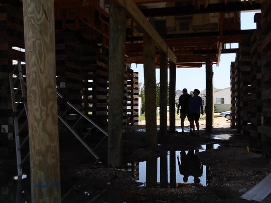 Amalia and Ralph DeNisco look over the lack of progress on their home in the Mystic Island section of Little Egg Harbor. Their home has been lifted but the home still has no floor and completion of work on the home is months behind schedule.