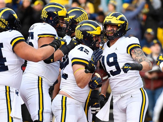 Michigan's Henry Poggi (19) is congratulated by Ben Mason (42) and more teammates after scoring a touchdown against Maryland in the first half Saturday, Nov 11, 2017 in College Park, Maryland.