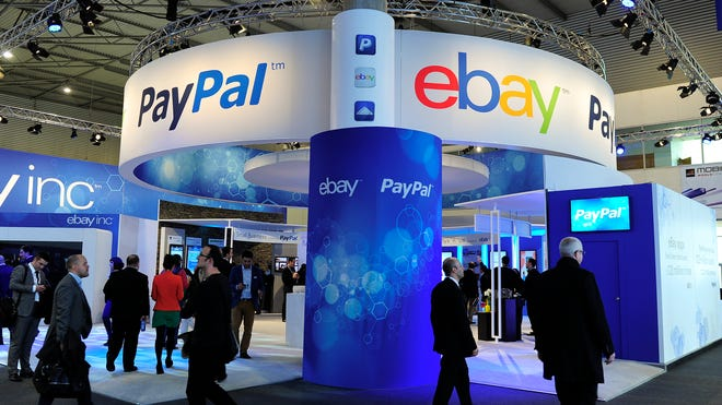 Visitors walk past an eBay and PayPal stand at the 2013 Mobile World Congress in Barcelona in 2013.