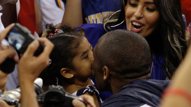 USA's Kobe Bryant gets a kiss from his daughter Gianna Maria-Onore as his wife Vanessa looks on as they celebrate after beating Spain 118-107 in the men's gold-medal basketball game at the Beijing Olympics. Gianna also died in the helicopter crash that killed Kobe on Sunday.