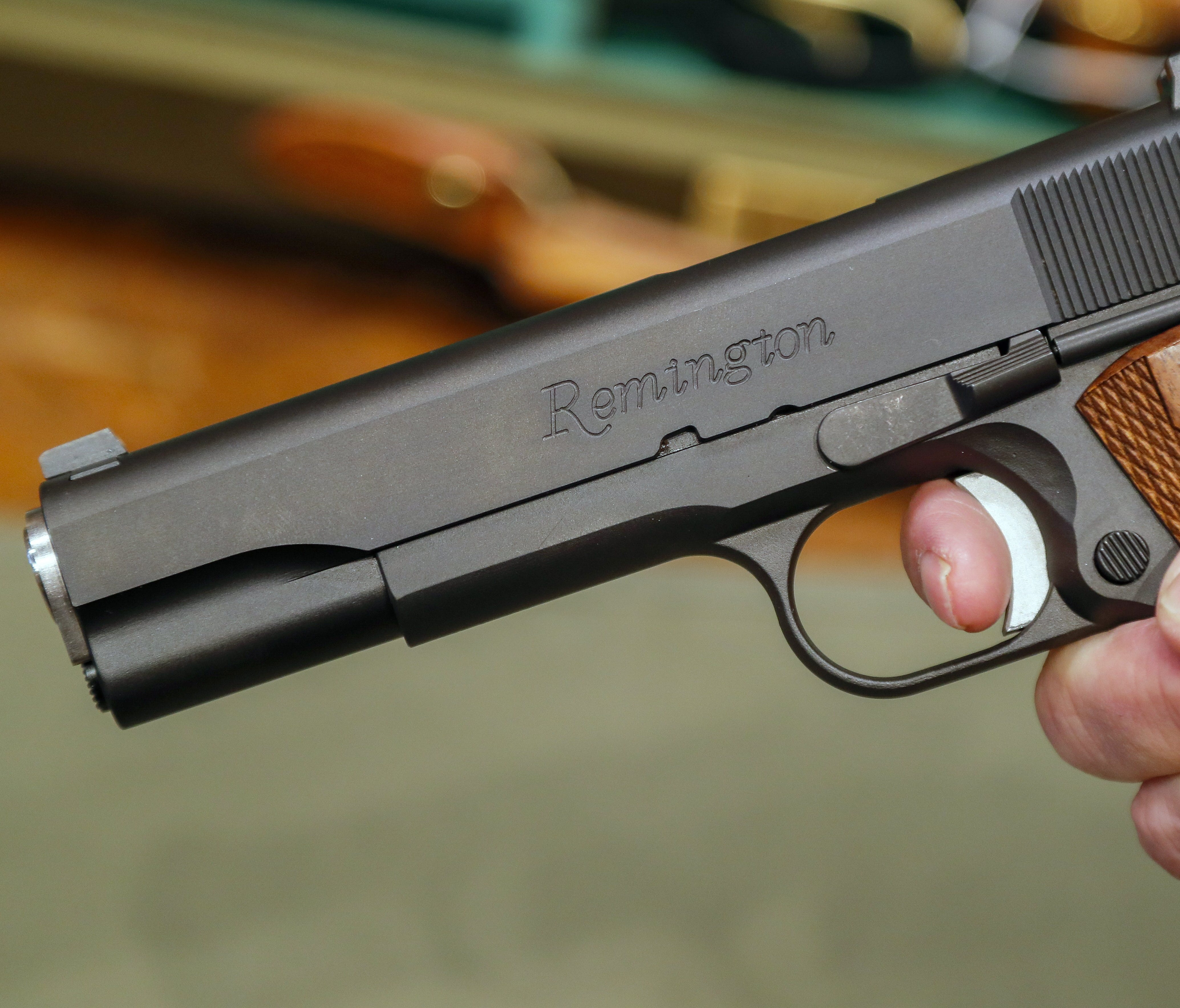 File picture: A salesperson holds a handgun at a firearms store.