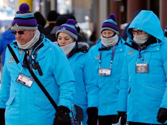 Super Bowl volunteers cross a street in Minneapolis