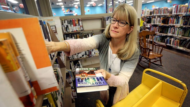 Lisa Robert, a library associate at the Linebaugh Library places reserved material on the reserved corner of the library, on Tuesday Dec. 1, 2015, for people to check out.