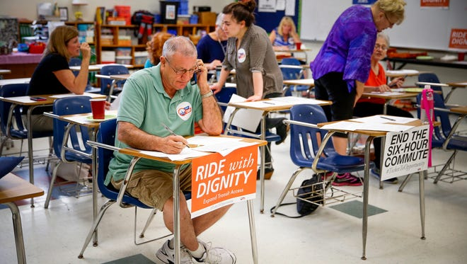 IndyCan volunteer Don Reed makes calls from a classroom in the basement of St. Monica Catholic Church on Wednesday, Aug. 17, 2016.