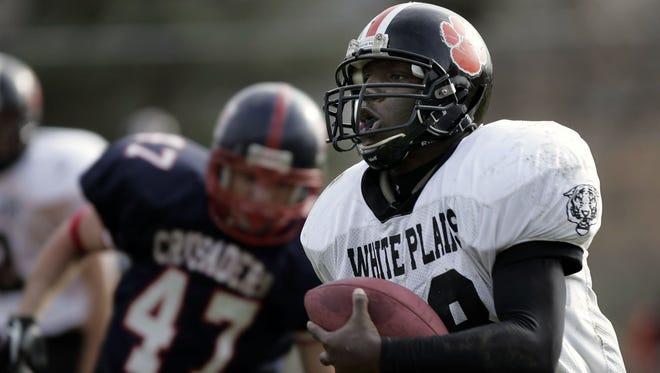 White Plains' Ike Nduka (28) looks for running room against Stepinac at Parker Stadium in White Plains on Nov. 25, 2004. White Plains won, 24-8.